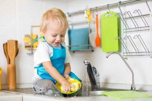 Washing Baby Feeding Supplies. Toddler washes dishes