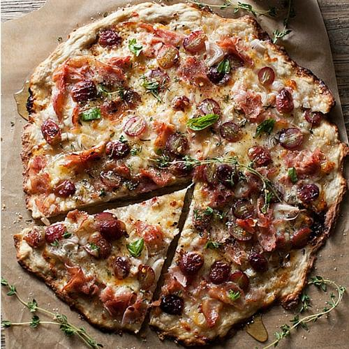 Rustic Pizza With Ham, Grapes, Shallots, Cheese, Honey And Thyme